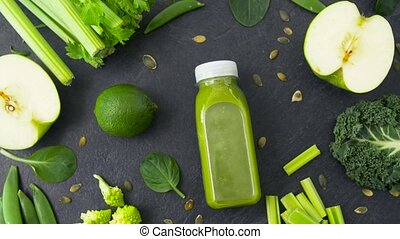 bottle with green juice and vegetables on table - healthy...