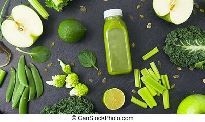 bottle with green juice and vegetables on table