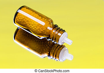 bottle with homeopathy globules laying on a mirror