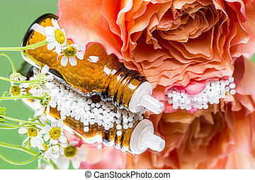 bottle with homeopathy globules laying on a mirror with flowers