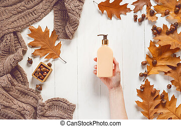 Bottle with liquid soap in female hands on white wooden background with a soft scarf and oak leaves. View from above. The concept of beauty and care for body and hands.