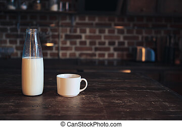 Bottle with milk and a cup on a wooden table