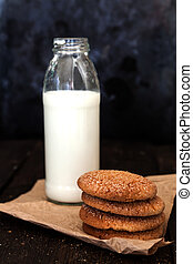 Bottle with milk and a stack of cookies on a dark background, re