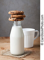 Bottle with milk and chocolate chip cookies on dark background