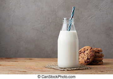 Bottle with milk and chocolate chip cookies on dark background with copy space