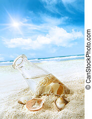 Bottle with seashells in the sand at the beach