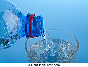 bottle with water and a glass on a blue background