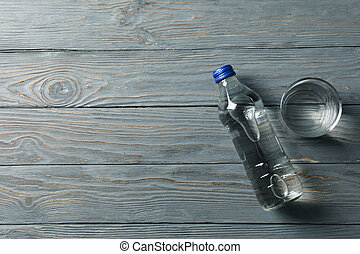 Bottle with water and glass on wooden background, space for text