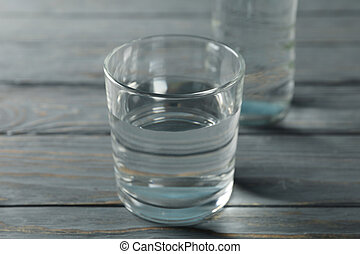 Bottle with water and glass on wooden table, close up