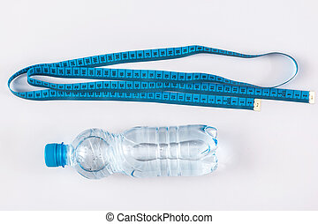 Bottle with water and measure tape on white background