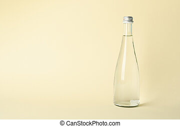 Bottle with water on beige background, space for text