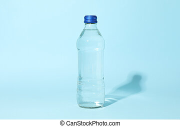 Bottle with water on blue background, space for text