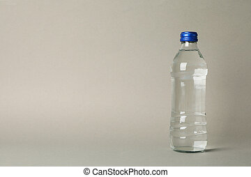 Bottle with water on gray background, space for text