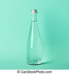 Bottle with water on mint background, space for text