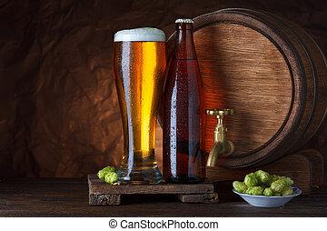 Bottled and unbottled beer glass with barrel and fresh hops...