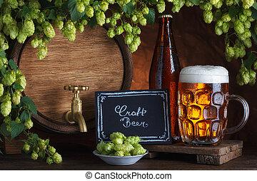 Bottled and unbottled beer with barrel and fresh hops for...