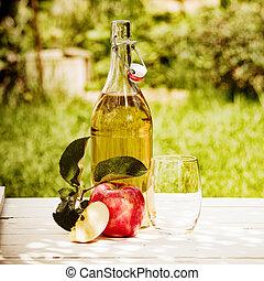 Bottled fresh apple juice served in the garden