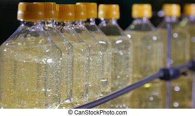 Bottled sunflower oil movng in conveyor stripe cheery in the...