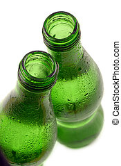 bottled water in green, condensation-covered bottles; isolated against white ground; differential focus