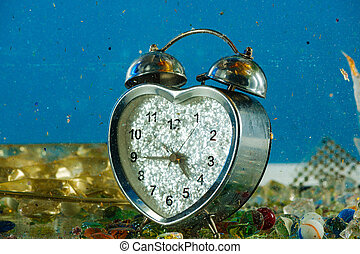 Broken heart shaped clock brightly sparkling while staying in trash