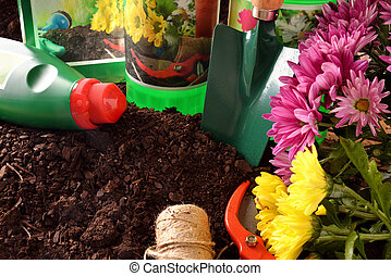 Bottles and containers gardening products on soil elevated view