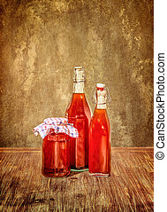 Bottles filled with yellow syrup and jam on kitchen table