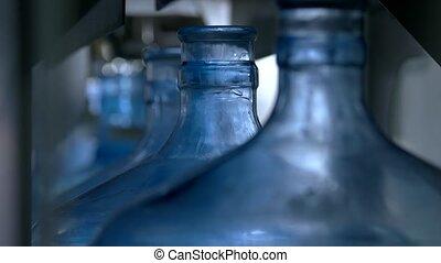Bottles moving on conveyor.