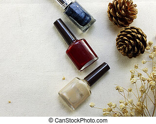 bottles nail polish on fabric background top view
