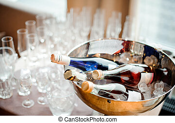 Bottles of alcoholic beverages and set of empty glasses on the table