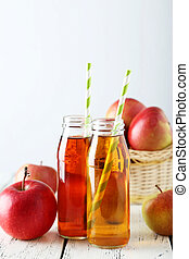Bottles of apple juice with apples on white wooden background