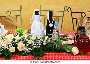 Bottles of champagne wine dressed in wedding gowns stand on festive table
