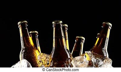 Bottles of dark cold beer in the ice. Black background....