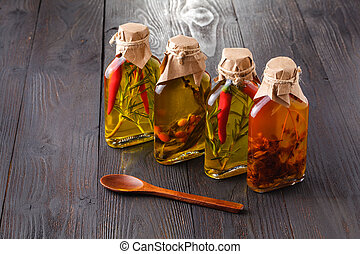 Bottles of extra virgin olive oil with aromatic herbs