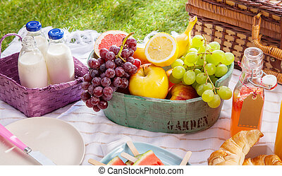 Bottles of fresh milk, juice and fruit at a picnic