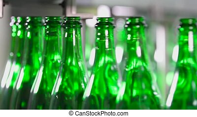 Bottles of green are moving along the conveyor