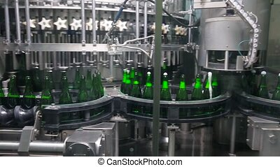 Bottles of green color move along conveyor at the factory of...