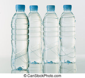 bottles of mineral water on white base with bright...