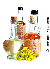 bottles of oil with rapeseed flower, on a white background
