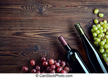 Bottles of red and white wine and grapes on wooden...