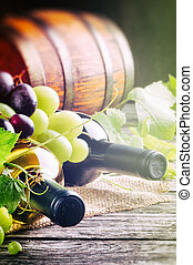 Bottles of red and white wine with fresh grape and wooden ...