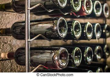 bottles of red wine on iron shelf