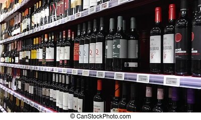 BARCELONA, SPAIN - NOVEMBER 7, 2019: Variety of wine in glass bottles on rack in supermarket