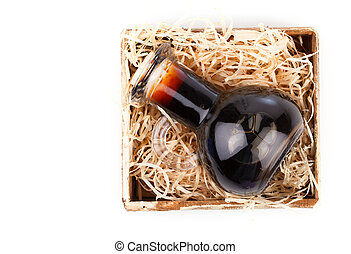 Bottles of wine or herbal syrup, in wooden box, over white background