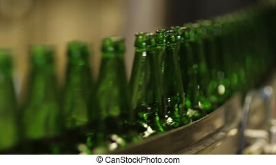Bottles on conveyor belt factory - Empty bottles of beer on...