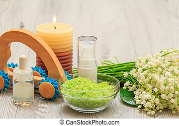 Bottles with cream for face skin and aromatic oil, bowl with sea salt, burning candle, hand massager and bouquet of lilies of the valley.