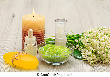 Bottles with cream for face skin and aromatic oil, bowl with sea salt, burning candle, soap and bouquet of lilies of the valley.
