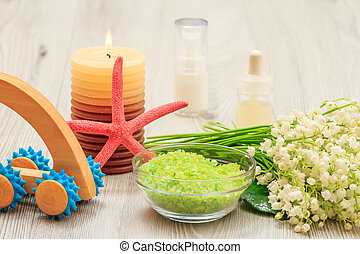Bottles with cream for face skin and aromatic oil, bowl with sea salt, burning candle, starfish, hand massager and bouquet of lilies of the valley.