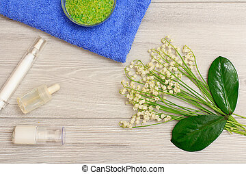 Bottles with cream for face skin and aromatic oil, bowl with sea salt on towel, green leaves and bouquet of lilies of the valley.