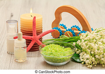 Bottles with cream for face skin and aromatic oil, sea salt and burning candle