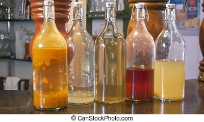 Bottles with different oil in restaurant at the bar, slider...